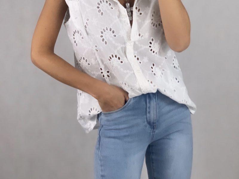 Blusa bordada sin mangas con detalle volantes en los hombros. Combinado con unos jeans de campana.